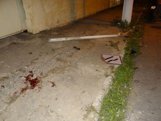 Marcas de sangue e placa derrubada faziam parte da cena do acidente (Foto: Thiago Gomes)