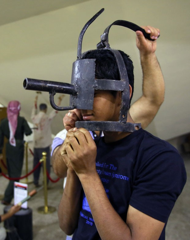 Jovem experimenta uma mãscara de tortura exposta no monumento Shaheed, em Bagdá (Foto: Ali al-Saadi/AFP)