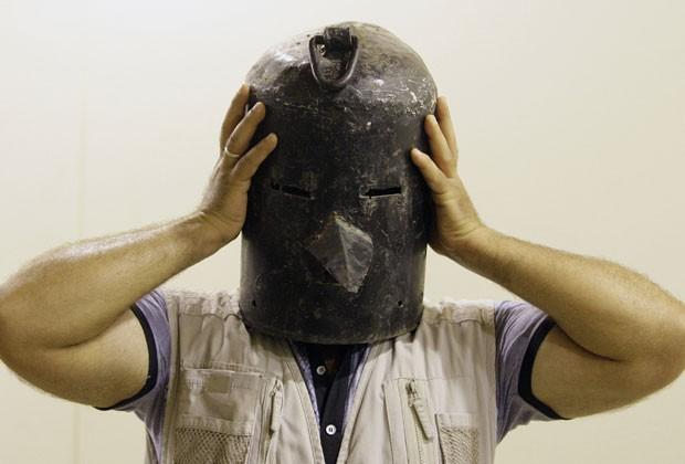 Iraquiano prova máscara de metal usada como objeto de tortura por Saddam Hussein (Foto: Khalid Mohammed/Reuters)