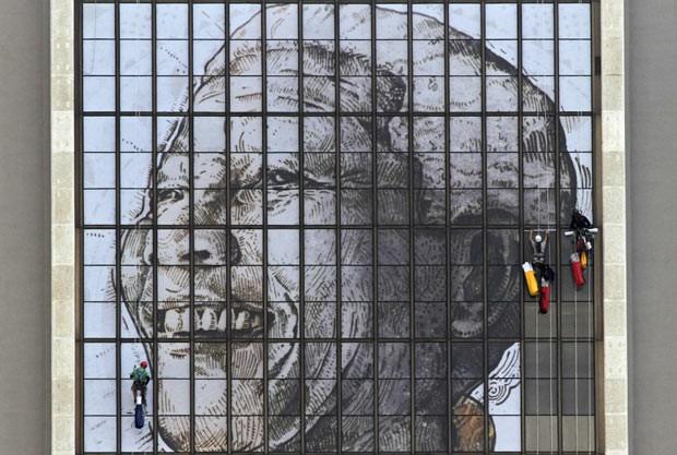 Operários preparam mural em homenagem a Nelson Mandela, neste sábado (15), no prédio do Centro Cívico, na Cidade do Cabo (Foto: AFP)