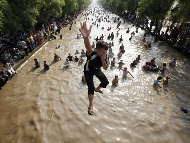 Crianças brincam em canal para refrescar o calor que atinge o Paquistão (Foto: Mohsin Raza/Reuters)