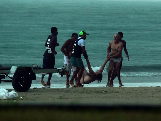 Banhistas socorrem a vítima na praia da Enseada, em Guarujá (Foto: Rogério Soares/Jornal A Tribuna)