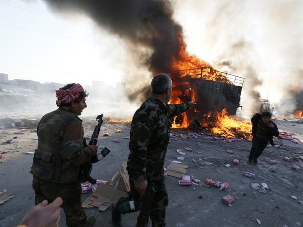 do rebelde Exército Livre Sírio reagem a um veículo queimado em um ataque aéreo do governo em Aleppo Foto: Reuters