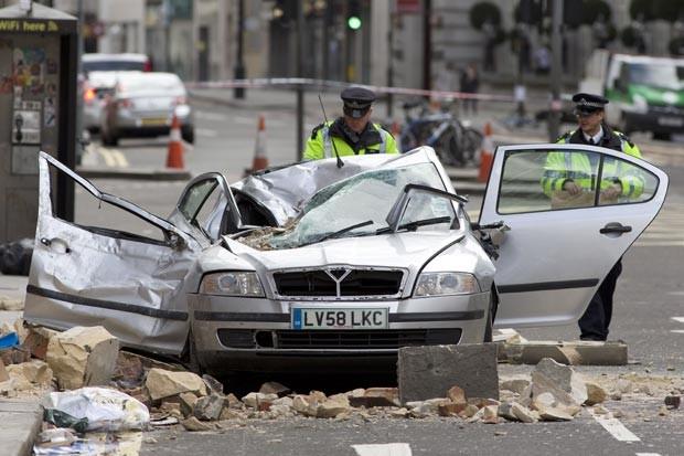 Carro ficou destruído após ser atingido pela parte do prédio derrubada pela ventania em Londres. Uma mulher morreu (Foto: Justin Tallis/AFP)