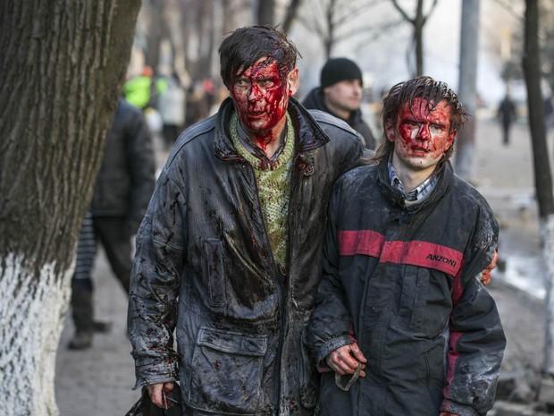 Feridos no confronto com a polícia caminham abraçados em Kiev (Foto: Vlad Sodel/Reuters)