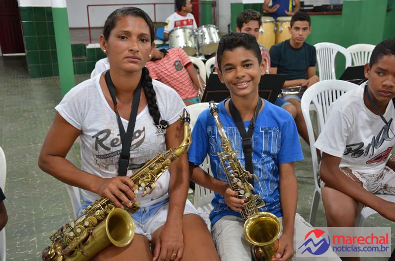 Quitéria e Alax, mãe e filho juntos no aprendizado musical.