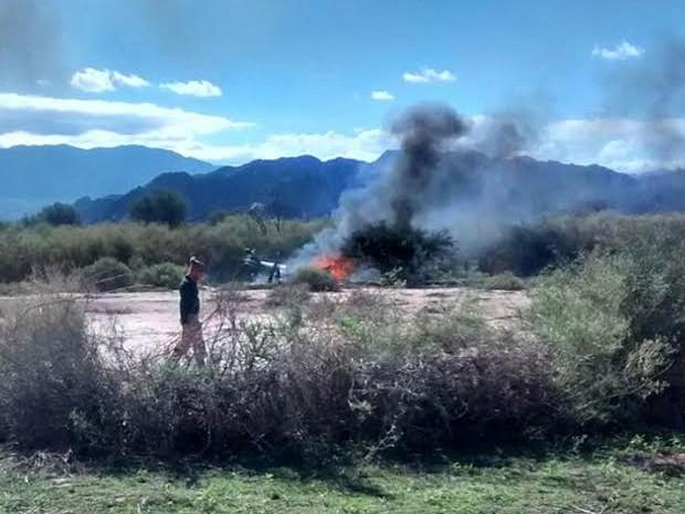 Homem passa em frente às chamas do que restou de um helicóptero envolvido no acidente aéreo envolvendo outro helicóptero durante gravação do reality show europeu 'Dropped' perto de Villa Castelli, na Argentina.