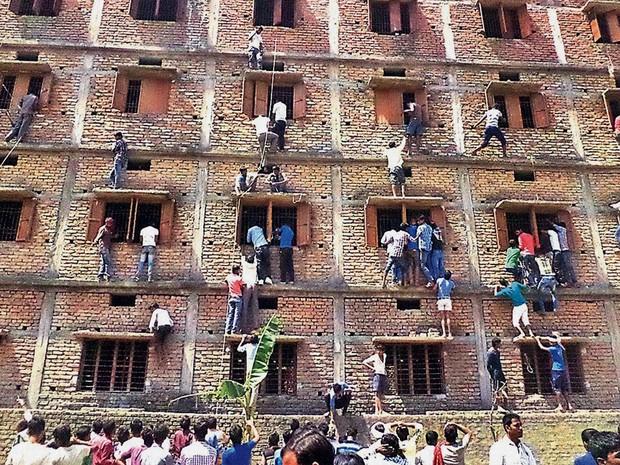 Pais e parentes de estudantes indianos escalam as janelas de uma escola para passar cola aos alunos na quarta-feira (18) na cidade de Hajipur, no leste da Índia